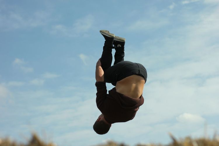Low angle view of person jumping against cloudy sky