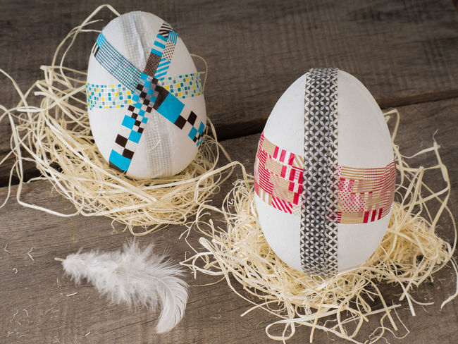 Two selfmade colored taped easter eggs on a wooden table with easter grass Celebration Colorful Creative Creativity Decoration Decorative Do It Yourself Easter Easter Eggs Eggs Event Fragility Gift Handicraft Holidays Homemade Huge Selfmade Spring Springtime Tape Tape Art Tinkering Wood Wooden