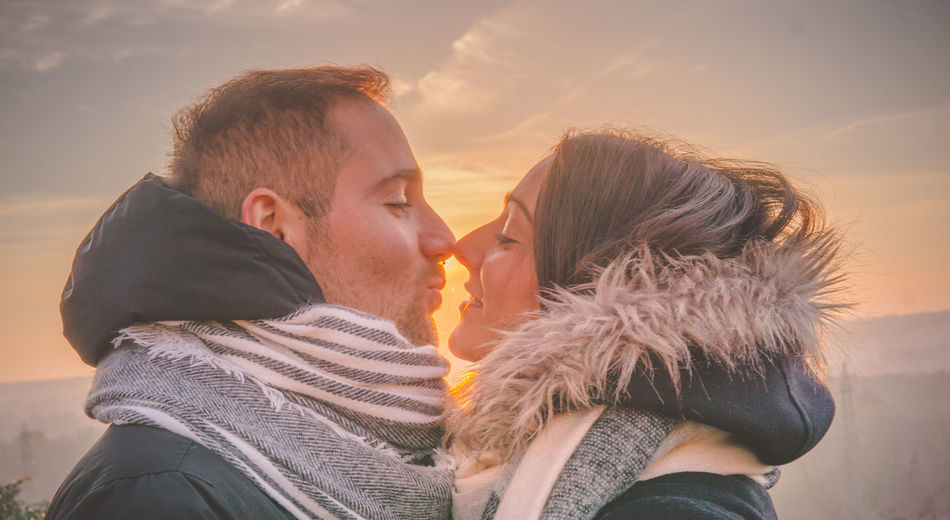 Close-Up Of Couple Kissing Against Sky During Sunset