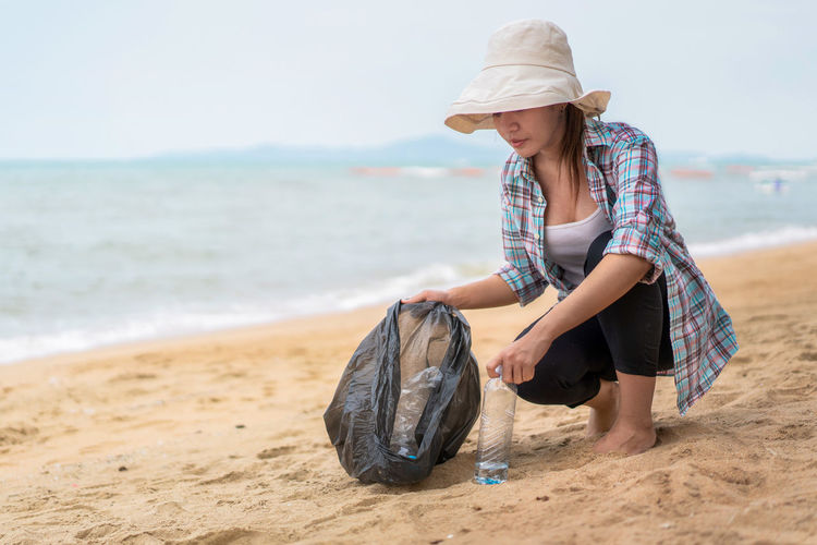 Woman collecting garbage at beach