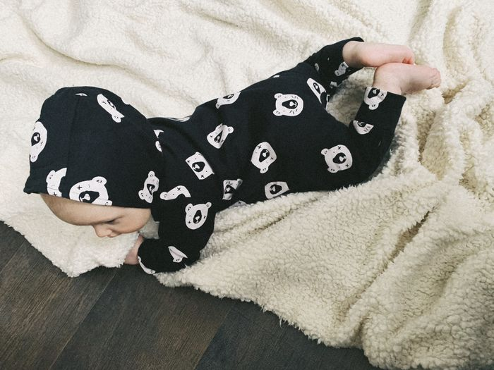 Indoors  One Person Real People High Angle View Lifestyles Clothing Leisure Activity Human Body Part Midsection Textile Representation Relaxation Casual Clothing Lying Down Unrecognizable Person Bed Furniture Close-up Softness Baby Boy Black Clothes Baby In Black Newborn