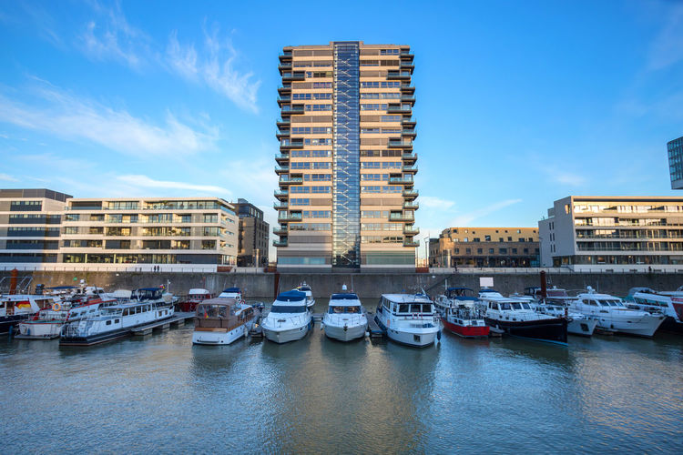 Boats moored at harbor by buildings against blue sky