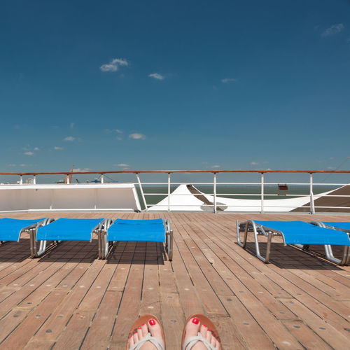 Low section of woman relaxing in cruise ship against sky