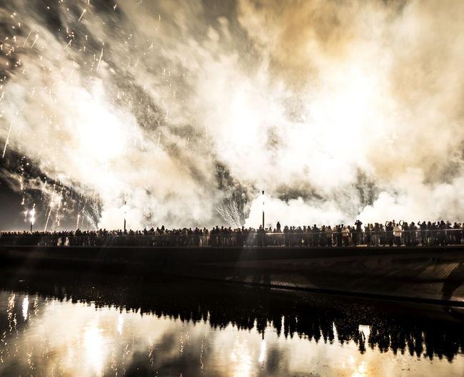 People on bridge over river against smoke