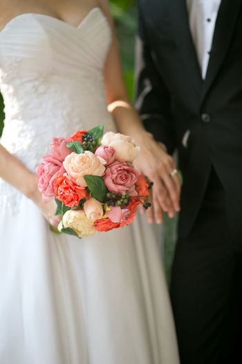 The midsection of the bride with bouquet holding the groom hand during the wedding ceremony Flower Wedding Bride Flowering Plant Newlywed Celebration Wedding Dress Event Bouquet Flower Arrangement Midsection Women Life Events Plant Love Ceremony Married Adult Holding Rose - Flower Wedding Ceremony Positive Emotion Hand Couple - Relationship Flower Bouquet