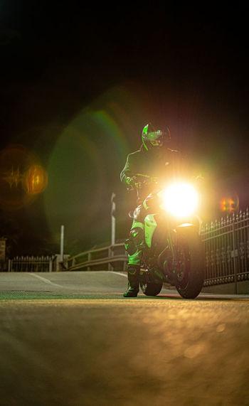 Man standing on illuminated road at night