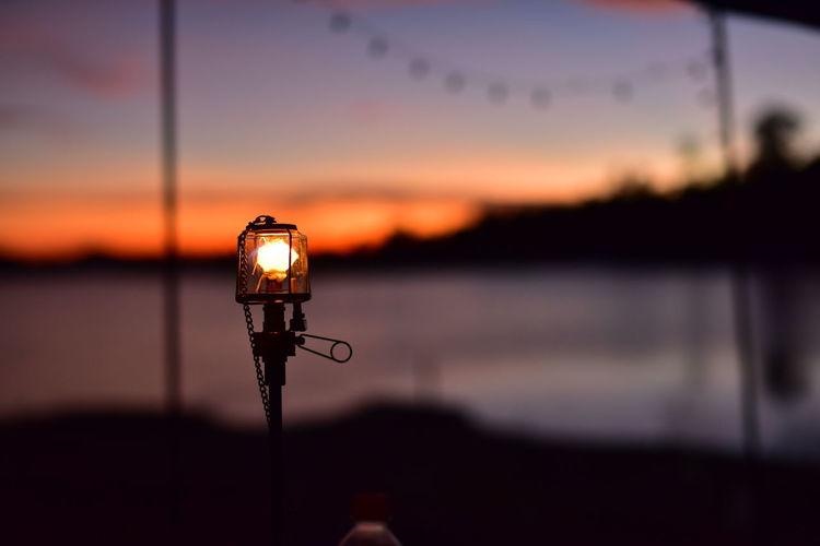 Close-up of illuminated lamp on lake against sky at sunset
