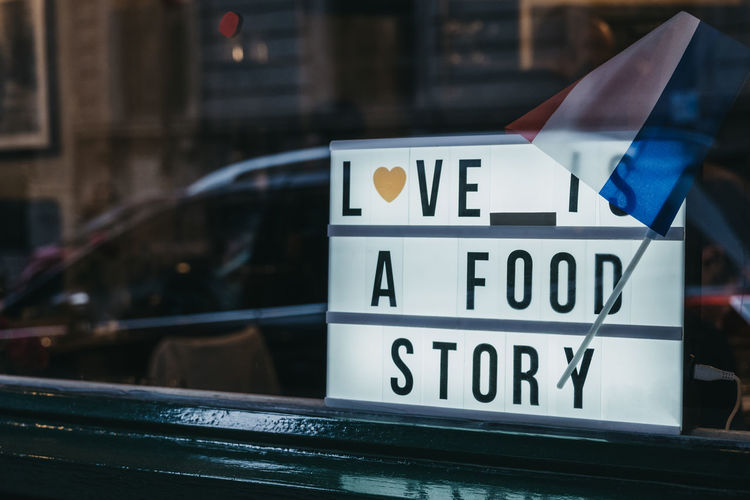 Close-up of love is a food story sign in the window of a restaurant.