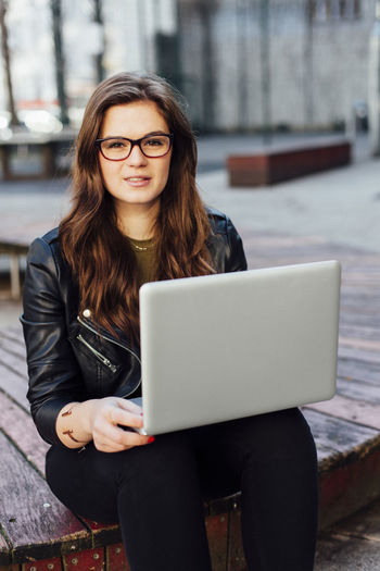 Portrait Of Young Woman Using Laptop On Wooden Bench