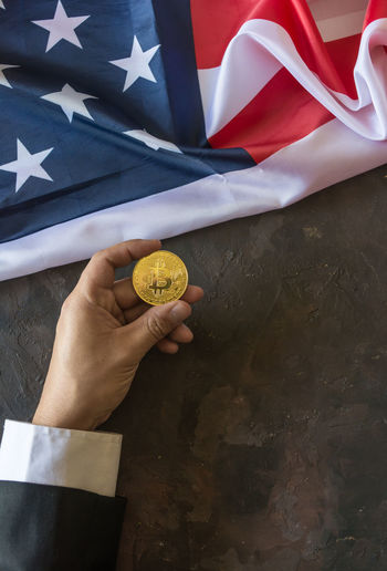 High angle view of hand holding bitcoin over american flag