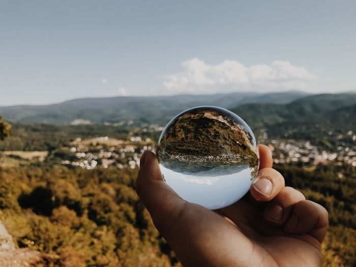 Cropped hand of person holding crystal ball on mountain against sky