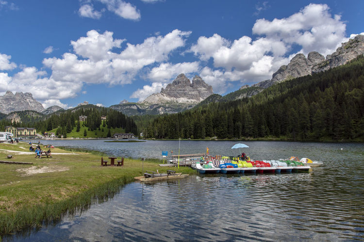 Beauty In Nature Cloud - Sky Day Group Of People Incidental People Lake Leisure Activity Misurina Lake Mode Of Transportation Mountain Mountain Range Nature Nautical Vessel Outdoors Plant Scenics - Nature Sky Tranquility Transportation Tree Water
