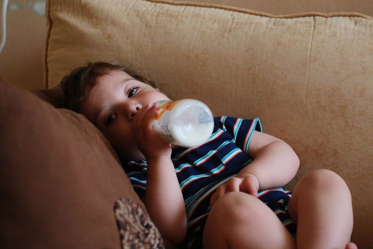 Boy Drinking Milk While Sitting On Sofa At Home