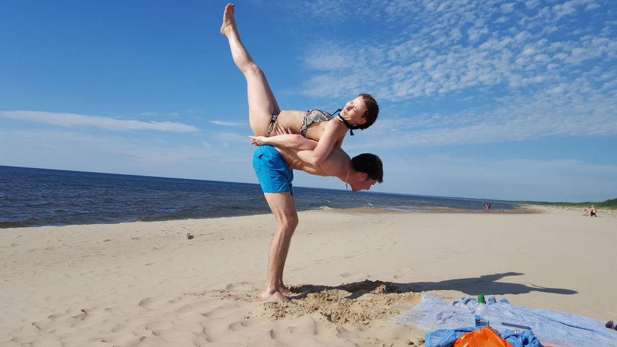 Man carrying woman while standing on sand at beach