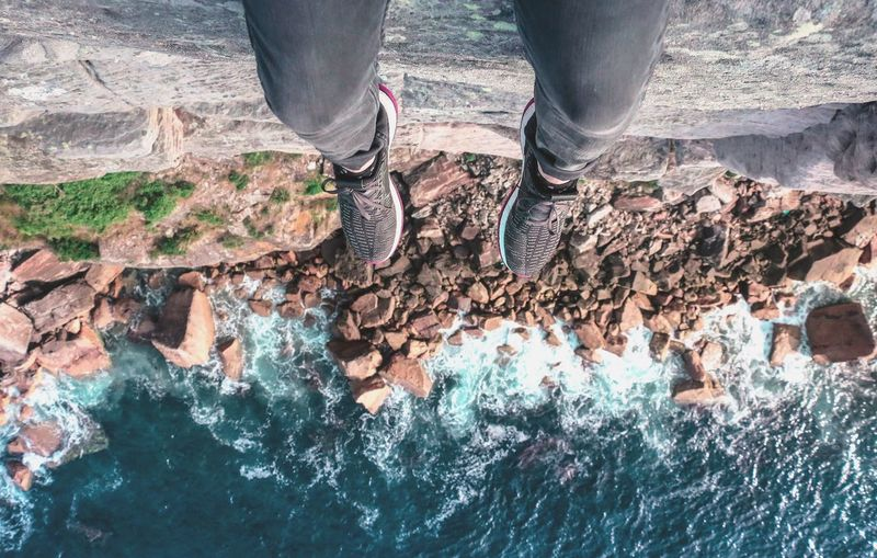 Low Section Of Person Dangling Legs Over Sea