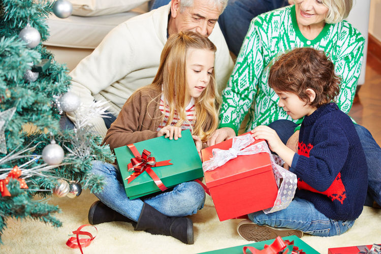 Cheerful brother and sister sitting with grandparents opening gifts at home during christmas