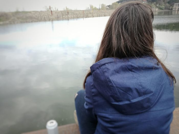 Rear View Water Lake Day One Person Only Women Women One Woman Only Adults Only Outdoors Adult Nature People Warm Clothing One Young Woman Only Sky Woman In Blue Beautiful Woman Blue Jeans Young Women Young Adult Adults Only Sitting Reflection Adult