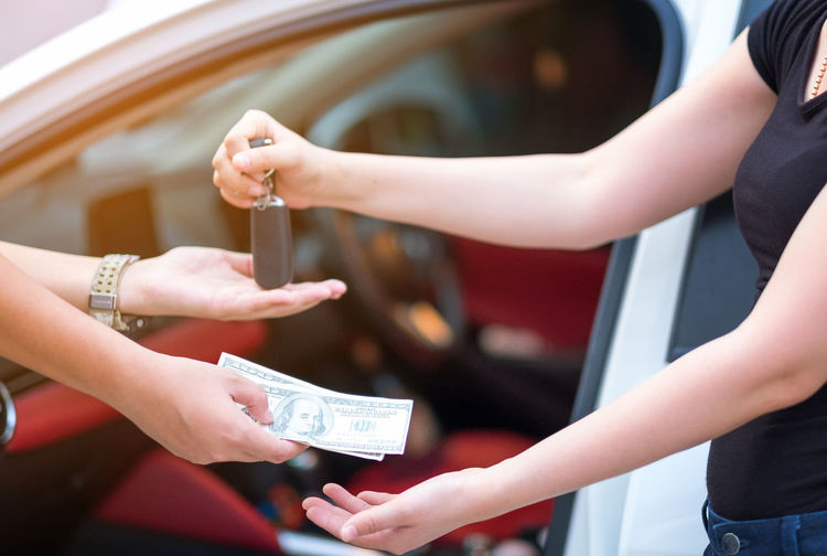 woman in showroom giving dollars money and taking keys from car Holding Real People Hand Human Hand Women Adult Lifestyles People Focus On Foreground Human Body Part Finance Day Midsection Giving Friendship Incidental People Leisure Activity Currency Finger Receiving Luxury Consumerism