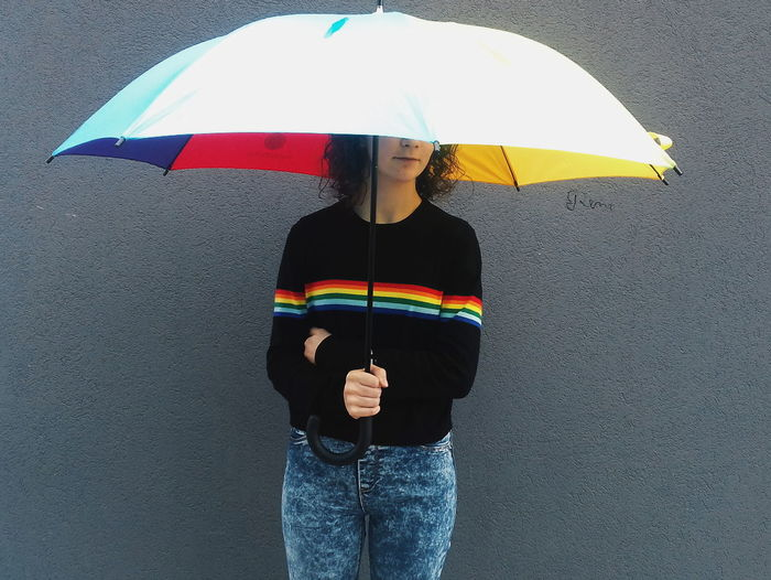 Woman Holding Umbrella While Standing Against Concrete Wall