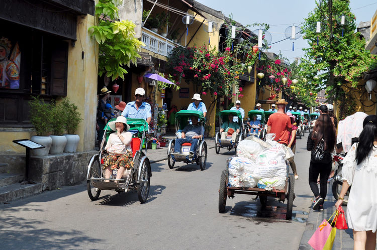 Cyclos with tourists in street in Hoi An, Vietnam. Architecture Carts Cyclo Hoi An In A Line Leisure Lifestyles Loads Outdoors Parade Shops Sightseeing Street Tourism Tourists Transport Tree Uniforms Vietnam