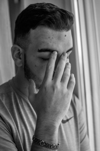 Sad young man sitting by window at home