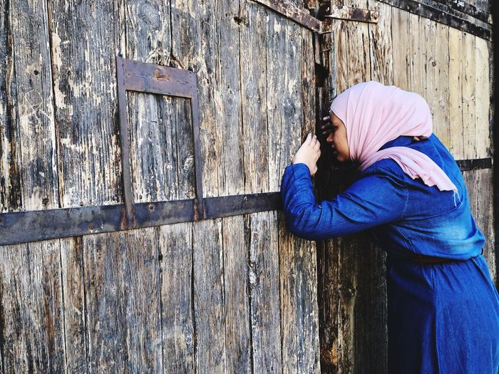 Woman Peeking Through Closed Wooden Gate