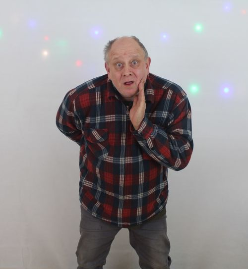 Portrait of shock man standing against illuminated wall