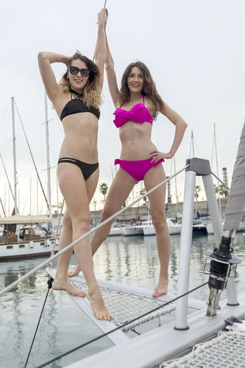 Low Angle View Of Happy Friends Wearing Bikini Standing On Boat In Sea Against Sky