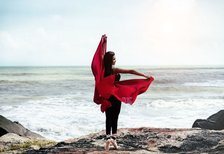 Woman holding scarf while dancing at beach against sky