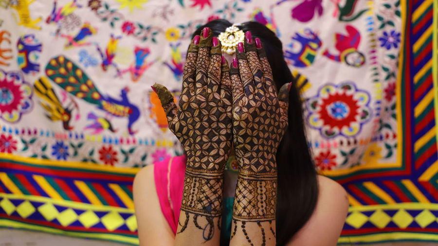 Close-up of bride with henna tattoo hiding face with hands