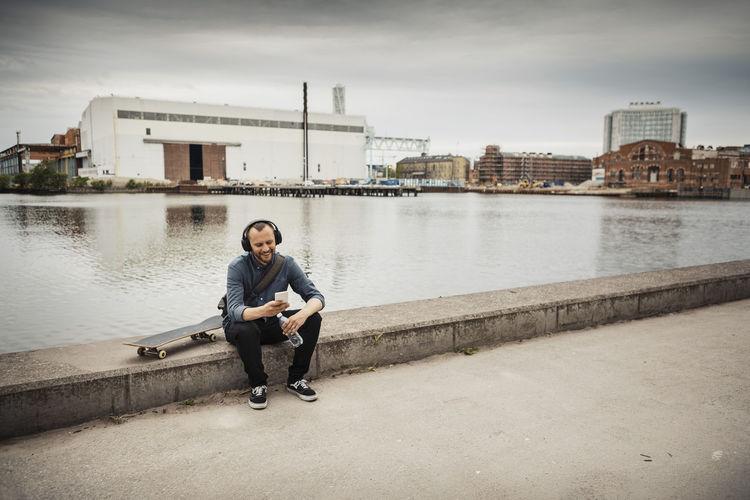 Full length of man sitting on riverbank against sky