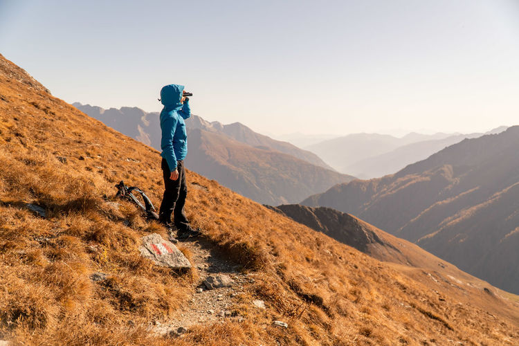 Full length of woman hiking on mountain against sky