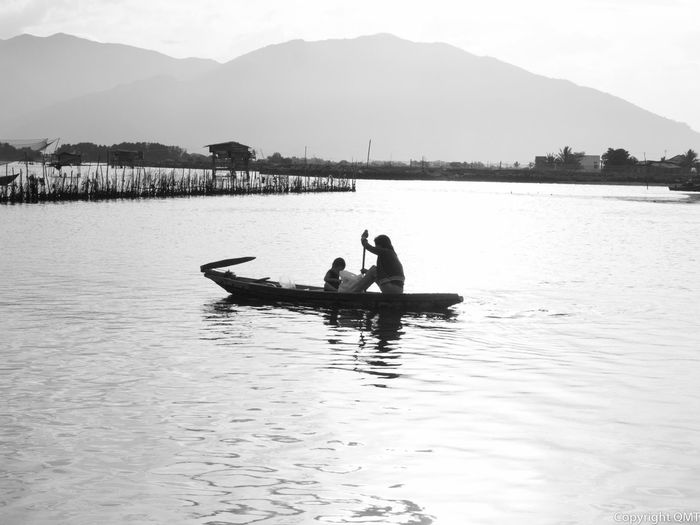Mother with son sailing on boat in river against mountains