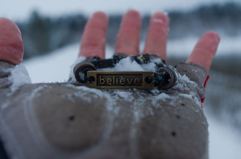 Close-up of hand holding text on snow