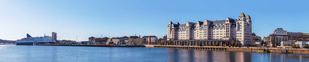 View of buildings by river against clear blue sky