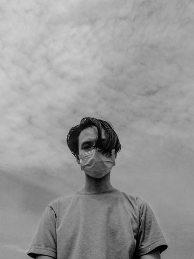 Portrait of man wearing mask standing against sky