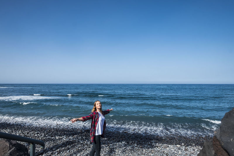 Woman with arms outstretched standing at beach against clear blue sky