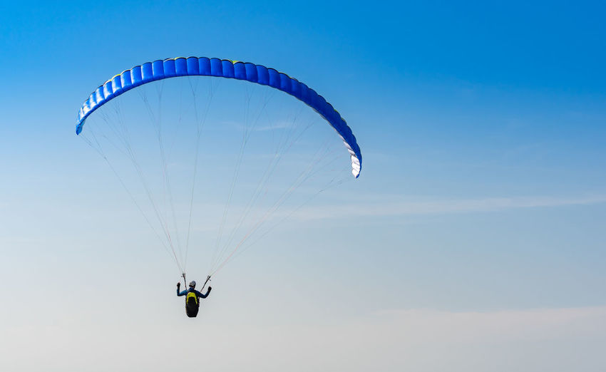 Low angle view of man paragliding against blue sky
