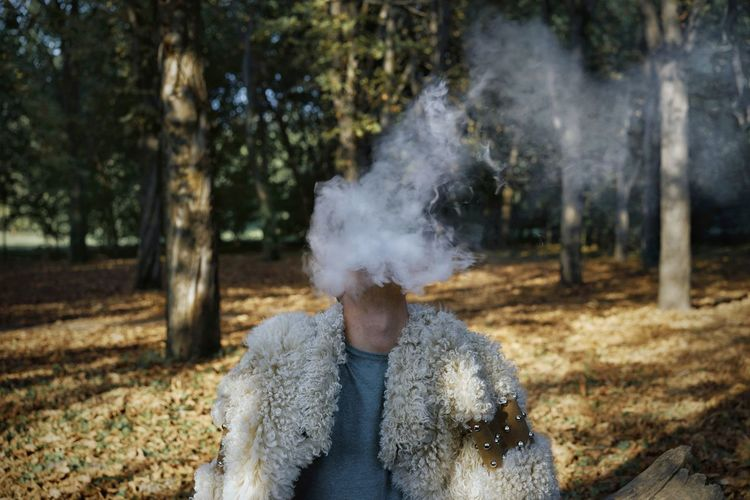 Man smoking while sitting in forest