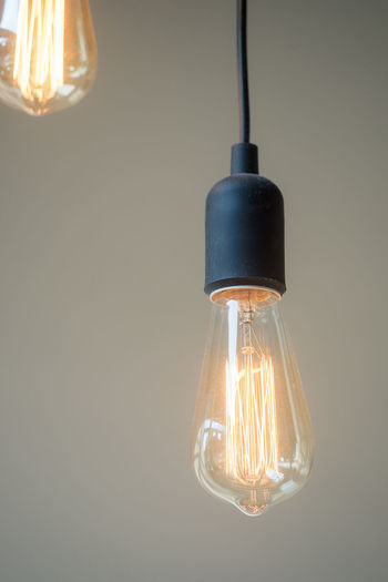 Close-up of illuminated light bulb hanging from ceiling