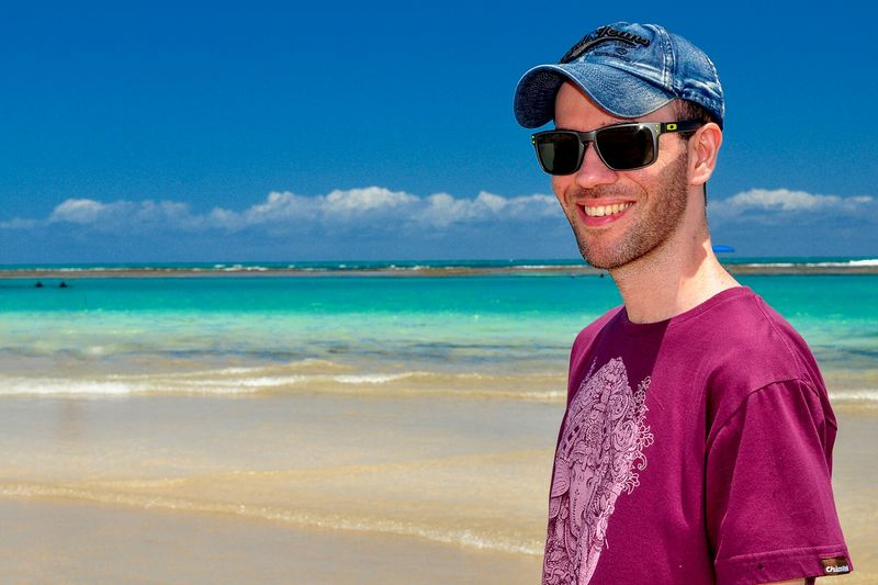 Smiling man standing at beach against sky
