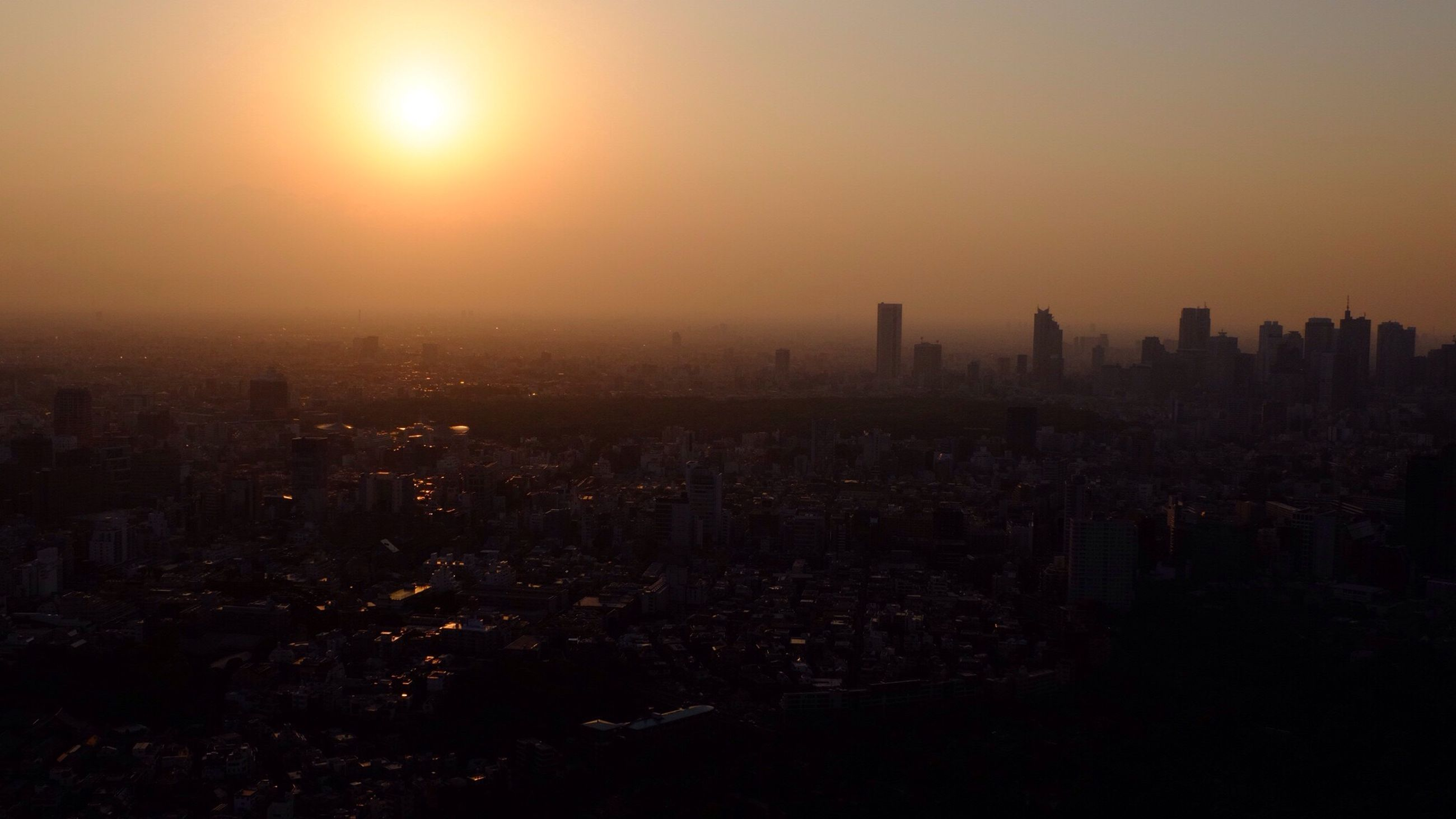 cityscape, sunset, city, building exterior, architecture, built structure, crowded, skyscraper, sun, orange color, high angle view, sky, residential district, clear sky, residential building, tower, urban skyline, city life, tall - high, sunlight