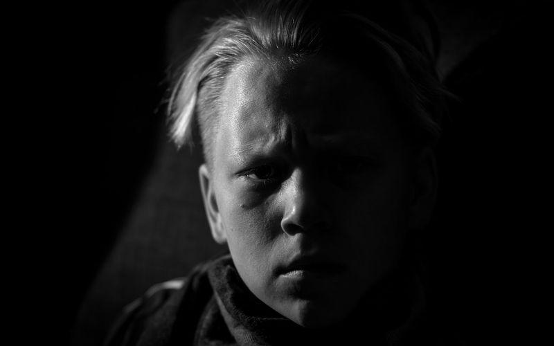 Close-up portrait of serious boy in darkroom