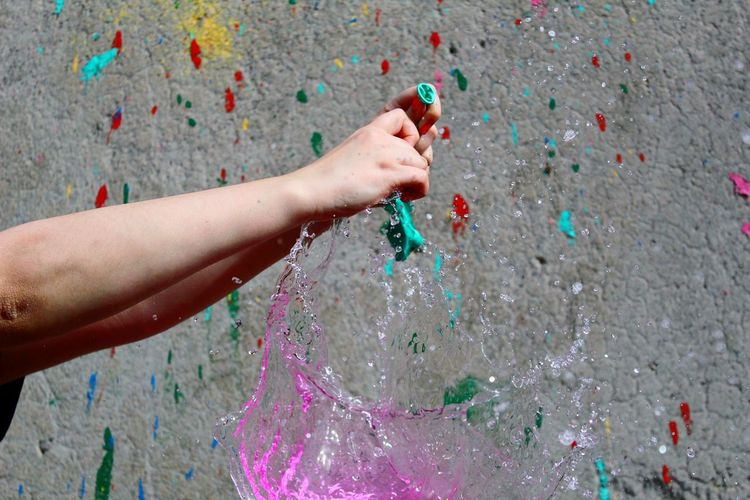 Cropped image of hand bursting water balloon