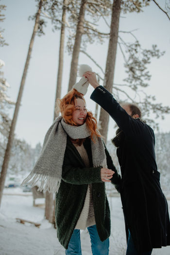 Smiling couple dancing while standing during winter in forest