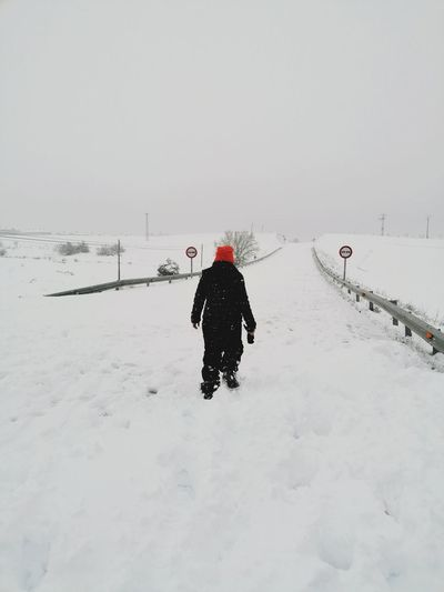 Rear view of people on snow covered field against sky
