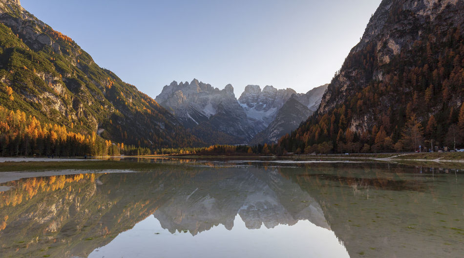 Scenic view of lake and mountains against clear sky in dolomites mountains