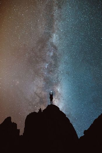 Low Angle View Of Silhouette Person Standing On Mountain Against Star Field