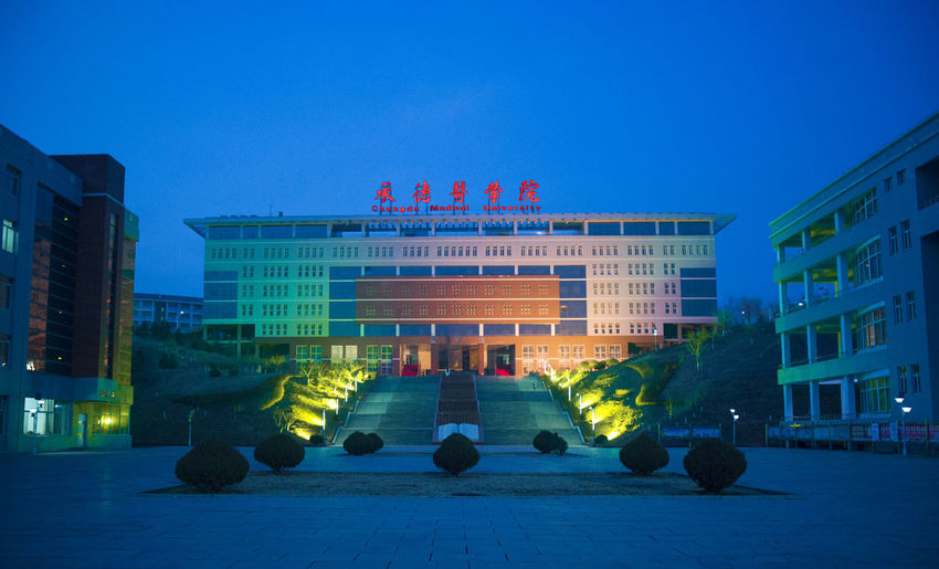People in illuminated building against blue sky