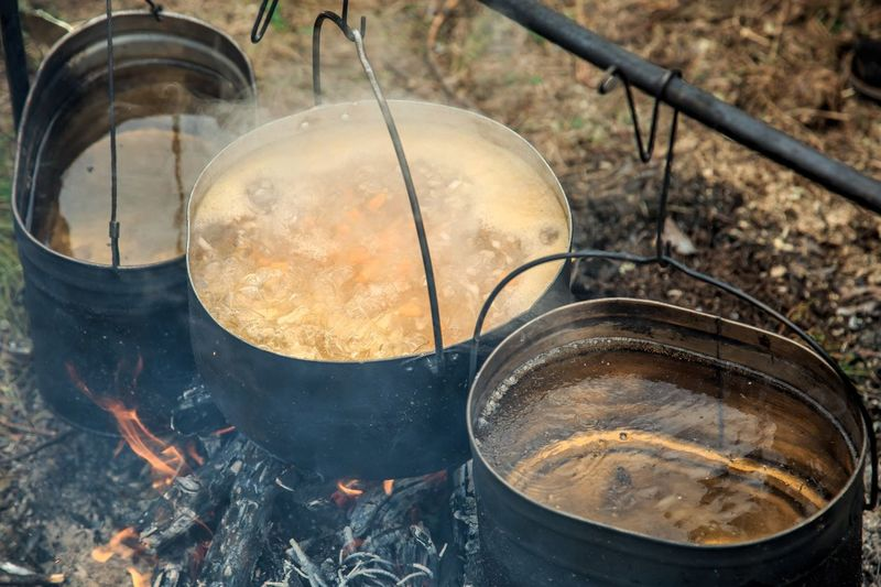 High angle view of food cooking in containers on wood burning stove